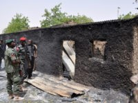 Anti-riot policemen look at a burnt mud house in Gubio in Borno State, northeast Nigeria, on May 26, 2015. A weekend attack by Boko Haram in the northeast Nigerian town of Gubio left 37 people dead, with more than 400 buildings destroyed by fire, local vigilantes said on May 26. …