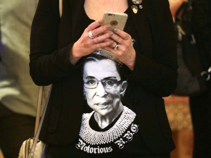 Laura Taylor wears a shirt with a likeness of U.S. Supreme Court justice Ruth Bader Ginsburg as she checks returns at an election night party for Democrats Tuesday, Nov. 6, 2018, in Bellevue, Wash. (AP Photo/Elaine Thompson)