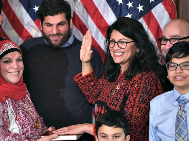 US House Representative Rashida Tlaib (D-MI), wearing a traditional Palestinian robe, takes the oath of office on Thomas Jefferson's English translated Quran, with family members present in a ceremonial swearing-in from Speaker of the House Nancy Pelosi (D-CA) (out of frame) at the start of the 116th Congress at the …