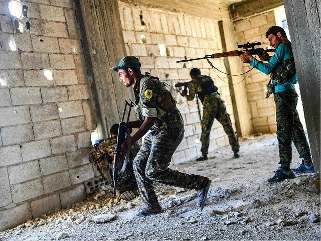 Members of the Syrian Democratic Forces fire their arms during a battle against Islamic State (IS) group jihadists to retake the central hospital of Raqa on the western frontline of the city on September 28, 2017. Syrian fighters backed by US special forces are battling to clear the last remaining …