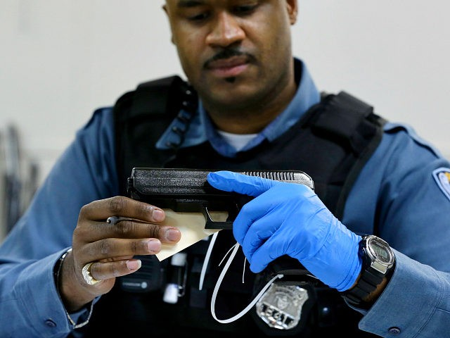 Trenton police officer Kozell Hodges examines a pistol Friday, Jan. 25, 2013, in Trenton, N.J., during a gun buy back program. New Jersey's latest gun buyback program is being held Friday and Saturday at two churches in Trenton, the state capital. At a similar program in Camden last month, people …