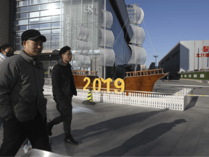 In this Friday, Jan. 4, 2019, photo, Chinese residents pass by a decor marking the new year outside a shopping mall in Beijing. A U.S. delegation led by deputy U.S. trade representative, Jeffrey D. Gerrish arrived in the Chinese capital ahead of trade talks with China. China sounded a positive …