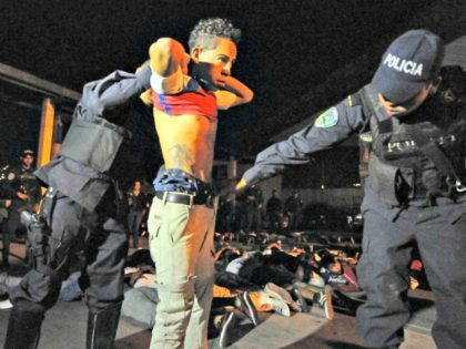 "Honduran policemen frisk a young man belonging to the Olympia club's Ultrafiel fans group, notoriously infiltrated by the ""maras"" (juvenile gangs), in Tegucigalpa, on February 10, 2013."