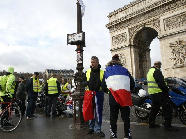 Yellow vest demonstrators gather near the Arc de Triomphe before marching in Paris, Saturday, Jan. 26, 2019. France's yellow vest protesters are hitting the streets again, keeping up pressure on President Emmanuel Macron even as internal divisions and frustration over protest violence cloud the movement's future. (AP Photo/Michel Euler)