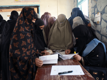 An Afghan Independent Election Commission (IEC) official (R) prepares ballot papers for voters at a polling centre for the country's legislative election in Kandahar province on October 27, 2018. - Afghans risked their lives to vote in legislative elections in southern Afghanistan on October 27, after the Taliban-claimed killing of …