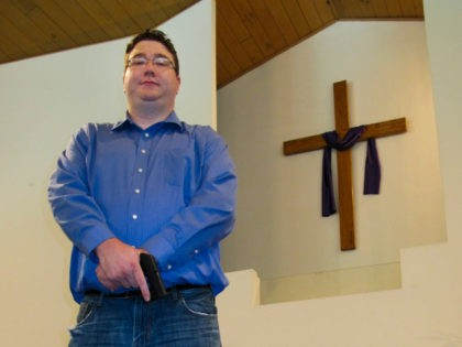 Pastor Cory Respondek poses with his Ruger handgun at his Living Water Church in Cahokia, Ill., just east of St. Louis, on Friday, Aug. 2, 2013. An Illinois state lawmaker is proposing adding churches to a list of places where firearms toted publicly under the state's new concealed-carry law would …