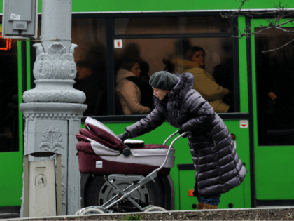 A mother carries a baby carriage as Italian and Belarus flags wave in central Minsk on November 30, 2009. Italian Prime Minister Silvio Berlusconi arrived in Belarus on Monday, making the first visit by a Western leader in 15 years to the country once dubbed 'Europe's last dictatorship.' AFP PHOTO …