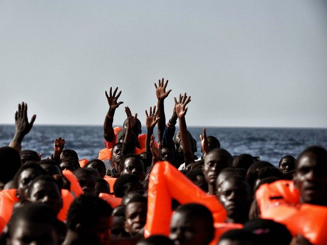 TOPSHOT - Migrants wait to be rescued as they drift in the Mediterranean Sea some 20 nautical miles north off the coast of Libya on October 3, 2016. Italy coordinated the rescue of more than 5,600 migrants off Libya, three years to the day after 366 people died in a …