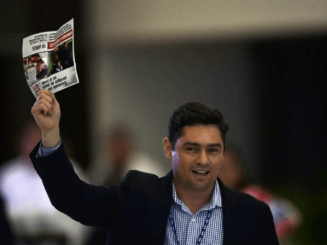 Exiled Venezuelan opposition leader Carlos Vecchio, holding up a newspaper article about one of the people killed in the opposition demonstrations in Venezuela, protests during the 47th General Assembly of the Organization of American States (OAS) in Cancun, Mexico on June 21, 2017. / AFP PHOTO / Pedro Pardo (Photo …