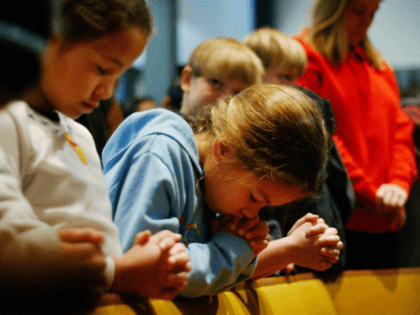 Susan (no last names released) bows her head in prayer as she and fellow fourth-grader Carolyne (L) attend a prayer service to give thanks that no one has died since a car plowed into 12 children, including Vanessa, and three teachers the day before at Westminster Academy Christian Day School, …