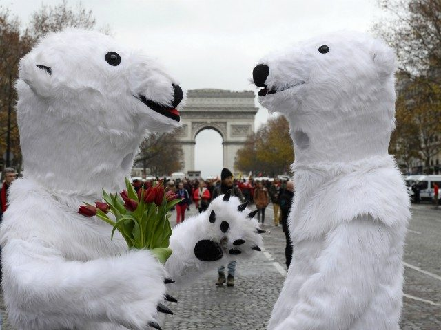 TOPSHOT - Activists dressed as polar bears are pictured as activists gather for a demonstration to form a giant red line at the Avenue de la Grande armee boulevard in Paris on December 12, 2015, as a proposed 195-nation accord to curb emissions of the heat-trapping gases that threaten to …
