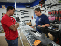 POMPANO BEACH, FL - JANUARY 16: Jonathan Schwartz (R), a salesman at the National Armory gun store, fills out the paperwork for Reese Magnant as he buys a National Armory AR-15 Battle Entry Assault Rife on January 16, 2013 in Pompano Beach, Florida. President Barack Obama today in Washington, DC …