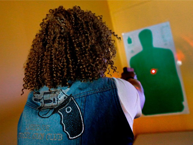 Javondlynn Dunagan of JMD Defense and Investigations demonstrates the laser on a Shot Indicating Resetting Trigger (SIRT) Training Pistol in her training classroom in Chicago, Illinois, July 19, 2017. (Photo by JIM YOUNG / AFP) / With AFP Story by Nova SAFO: A gun club for Chicago women concerned about …