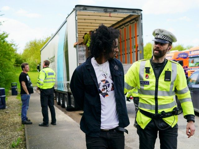 OXFORD, ENGLAND - MAY 03: Police officers arrest two men, believed to be migrants, who were stowed away in the back of a Polish lorry at Oxford Services on the M40 motorway on May 3, 2018 in Oxford, England. The truck was escorted off the M40 motorway by police where …