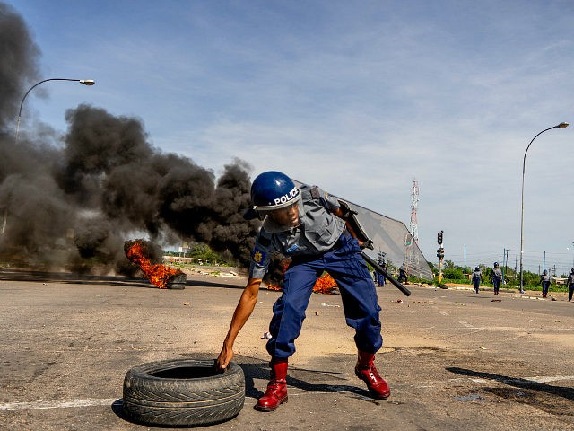 TOPSHOT - A police officer removes tyres set by protesters during a 'stay-away' demonstration against the doubling of fuel prices on January 14, 2019 in Emakhandeni township, Bulawayo. - Zimbabwe's President on January 12 announced a more than 100 percent rise in the price of petrol and diesel in a …