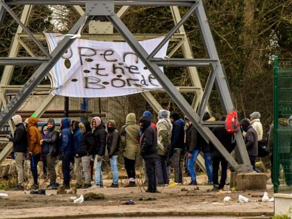 Migrants queue during a food distribution by an association helping migrants in Calais, on February 2, 2018, a day after a giant brawl between Afghans and Eritreans migrants left four of them fighting for their lives. Five migrants were shot during a clashes in Calais, in what the French government …