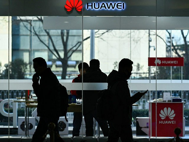 Pedestrians walk past a Huawei store in Beijing on December 28, 2018. - Chinese telecoms giant Huawei expects to see a 21 percent rise in revenue for 2018, its chairman said on December 27, despite a year of 'unfair treatment' which saw its products banned in several countries over security …