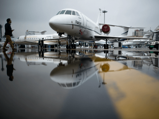 A man passes the Dassault Falcon 2000EX business jet before the start of the 2017 Asian Business Aviation Conference and Exhibition (ABACE) at Shanghai's Hongqiao Airport on April 10, 2017. ABACE will be held at Shanghai Hongqiao Airport from April 11 to 13. / AFP PHOTO / Johannes EISELE (Photo …