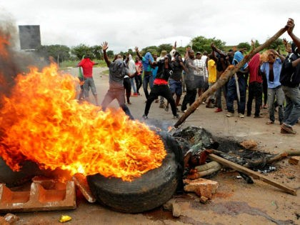 FILE - In this Tuesday, Jan. 15, 2019 file photo, protestors gather near a burning tire during a demonstration over the hike in fuel prices in Harare, Zimbabwe. 2019 is already a busy year for internet shutdowns in Africa, with governments ordering cutoffs as soon as a crisis appears. Zimbabwe …