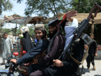Afghan Taliban militants ride a motorbike as they took to the street to celebrate ceasefire on the second day of Eid in the outskirts of Jalalabad on June 16, 2018. - Taliban fighters and Afghan security forces hugged and took selfies with each other in restive eastern Afghanistan on June …
