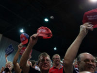 Supporters hold up their 'Make America Great Again' hats as US President Donald Trump speaks during a campaign rally at Florida State Fairgrounds Expo Hall in Tampa, Florida, on July 31, 2018. (Photo by SAUL LOEB / AFP) (Photo credit should read SAUL LOEB/AFP/Getty Images)