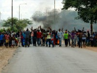 Angry protesters gesture as they block the main route to Zimbabwe's capital Harare from Epworth township on January 14 2019 after announced a more than hundred percent hike in fuel prices. - Angry protesters barricaded roads with burning tyres and rocks in Zimbabwe on January 14 after the government more …