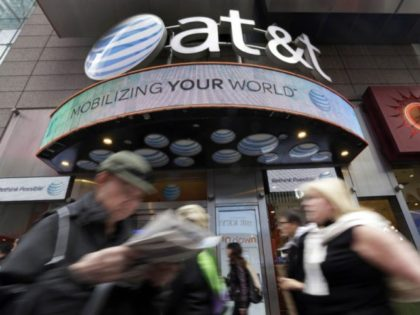 In this Oct. 21, 2014 file photo, people pass an AT&T store in New York's Times Square. AT&T says it will stop selling customer location data to data brokers, as the telecom industry faces backlash that the data has been used improperly. The company says it will eliminate even the …