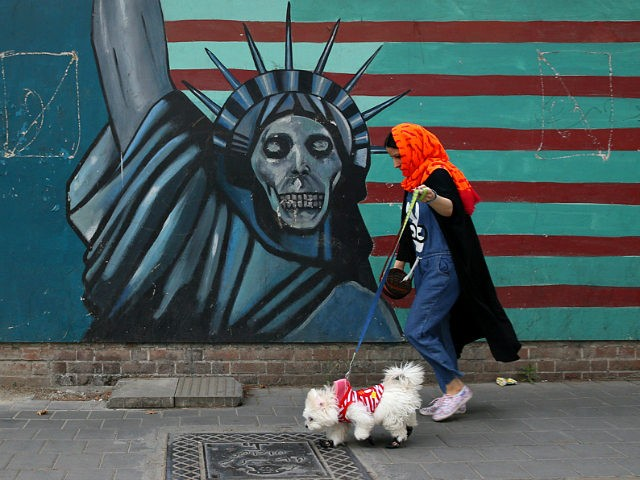 A woman walks her dog past an anti-U.S. mural painted on the wall of the former U.S. Embassy in Tehran, Iran, Tuesday, May. 8, 2018. President Donald Trump prepared to tell the world Tuesday whether he plans to follow through on his campaign threat to pull out of the landmark …