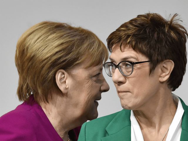 TOPSHOT - German Chancellor Angela Merkel (L) walks past her successor, newly- elected leader of the Germany's conservative Christian Democratic Union (CDU) party Annegret Kramp-Karrenbauer during the CDU congress on December 8, 2018 at a fair hall in Hamburg, northern Germany. (Photo by John MACDOUGALL / AFP) (Photo credit should …