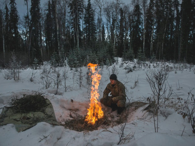 Staff Sgt. Seth Reab, an Arctic Survival School instructor, creates a small fire with a pile of tender branches during training. Fires can be used for signaling, heat and food during real-world survival situations.