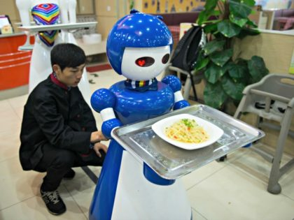 Robot waiters are seen working at a robot restaurant in Kunshan, China on May 22, 2016. The restaurant has a total of 10 robots in heights of 1.2 meters. Each robot costs 50,000 yuan and all used for delivery and cooking. Photo by Zhong Zhenbin — Anadolu Agency/Getty Images