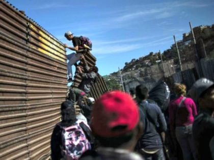 A group of Central American migrants climb the border fence between Mexico and the United States, near El Chaparral border crossing, in Tijuana, Mexico, Nov. 25, 2018. A group of Central American migrants climb the border fence between Mexico and the United States, near El Chaparral border crossing, in Tijuana, …