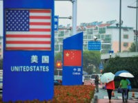 Signs with the US flag and Chinese flag are seen outside a store selling foreign goods in Qingdao in China's eastern Shandong province on September 19, 2018. - China on September 18 announced tariffs on US goods worth $60 billion in retaliation for President Donald Trump's decision to slap duties …