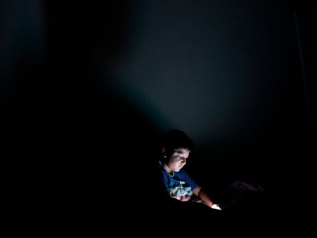 A child plays with a smartphone in his bedroom in San Salvador on October 7, 2018.