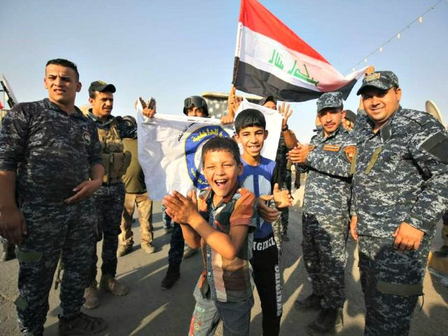"Iraqi federal police members and civilians celebrate in the Old City of Mosul on 9 July 2017 after the government's announcement of the ""liberation"" of the embattled city. Iraqi Prime Minister Haider al-Abadi's office said he was in ""liberated"" Mosul to congratulate ""the heroic fighters and the Iraqi people on …"