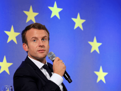 French President Emmanuel Macron speaks as he sits in front of a flag of the European Union during an open debate on Europe on October 10, 2017 at the Goethe University in Frankfurt am Main, western Germany. Macron takes his push for deeper European integration to Germany, where he and …