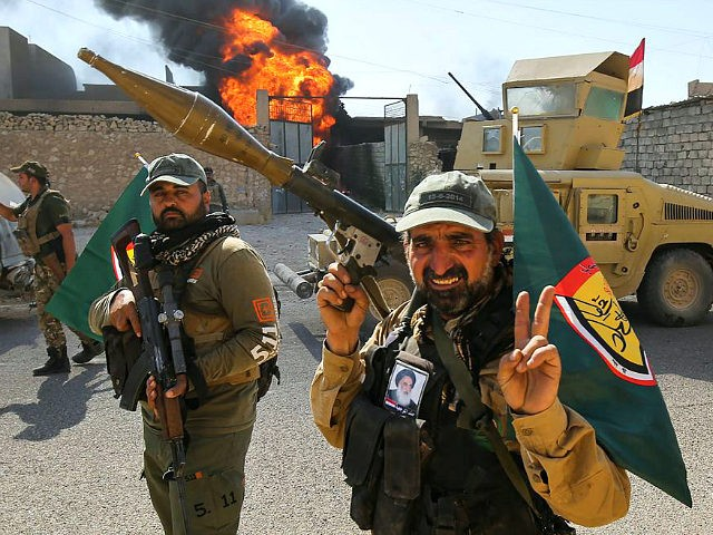Fighters of Hashed Al-Shaabi (Popular Mobilization units) flash the victory gesture as they advance through a street in the town of Tal Afar, west of Mosul, after the Iraqi government announced the launch of the operation to retake it from Islamic State (IS) group control, on August 26, 2017. / …