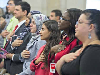 People recite the Pledge of Allegiance during a Naturalization Ceremony at the Justice Department in Washington, DC. Photograph by Saul Loeb—AFP/Getty Images