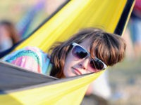 GLASTONBURY, ENGLAND - JUNE 24: A festival-goer relaxes in a hammock at sunset during Day 1 of the Glastonbury Festival on June 24, 2010 in Glastonbury, England. This year sees the 40th anniversary of the festival which was started by a dairy farmer, Michael Evis in 1970 and has grown …