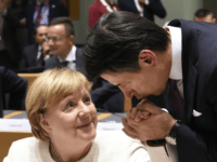 TOPSHOT - German Chancellor Angela Merkel (L) has her hand kissed by Italy's Prime Minister Giuseppe Conte (R) ahead of an Asia Europe Meeting (ASEM) at the European Council in Brussels on October 18, 2018. (Photo by JOHN THYS / AFP) (Photo credit should read JOHN THYS/AFP/Getty Images)