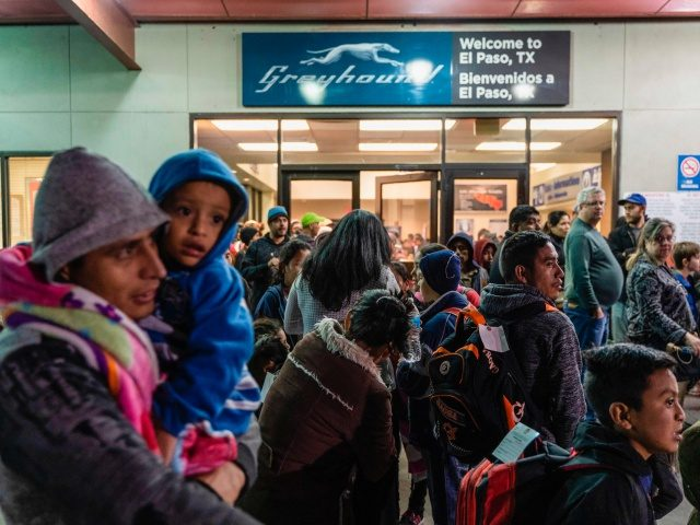 Asylum seekers stand at a bus stop after they were dropped off by Immigration and Customs Enforcement (ICE) at the Greyhound bus station in downtown El Paso, Texas late on December 23, 2018. - The group of around 200, mostly made up of Central Americans, were left without money, food …