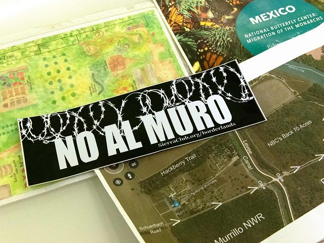 "A map of the National Butterfly Center (L bottom) next to a sticker reading ""No to the Wall,"" on January 15, 2019 in Mission, Texas. - The protected habitat of butterflies along the Rio Grande is expected to be plowed over to clear the way for President Trump's border wall …"