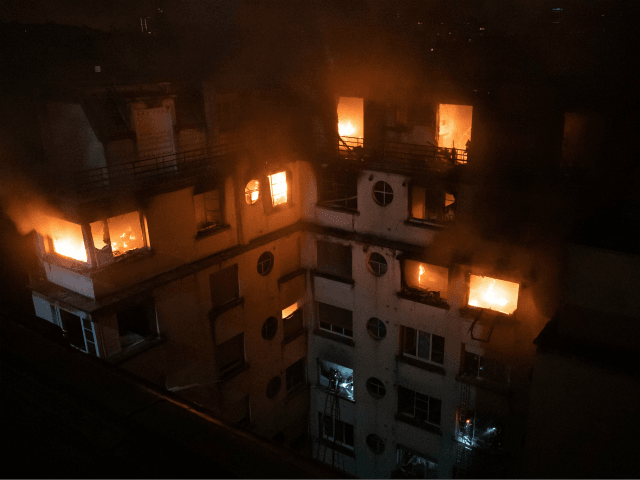 This handout picture taken and released by the Paris firefighters brigade (BSPP) in the night of February 5, 2019 shows a fire in a building in Erlanger street in the 16th arrondissement in Paris, that killed 8 people. - A woman has been arrested over a deadly blaze that killed …