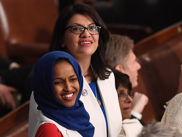 US Representative Ilhan Omar (D-MN) (L) and US Representative from Michigan Rashida Tlaib (D-MI), dressed in white in tribute to the women's suffrage movement, arrive for the State of the Union address at the US Capitol in Washington, DC, on February 5, 2019. (Photo by SAUL LOEB / AFP) (Photo …
