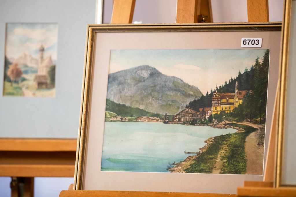 "A picture taken on February 8, 2019 shows the watercolour entitled ""Ortschaft an Vorgebirgssee"", a scene of a village near a mountain lake, signed ""A. Hitler"", which is on display at the Weidler auction house in the southern city of Nuremberg. - A German auction house scrapped the planned sale of 26 artworks attributed to Adolf Hitler, after doubts emerged about their authenticity just days before they were due to go under the hammer. Five paintings signed ""A. Hitler"", all of them watercolours, will be auctioned off on February 9, 2019 as scheduled, according to the Weidler auction house. (Photo by DANIEL KARMANN / AFP) / RESTRICTED TO EDITORIAL USE - TO ILLUSTRATE THE EVENT AS SPECIFIED IN THE CAPTION (Photo credit should read DANIEL KARMANN/AFP/Getty Images)"