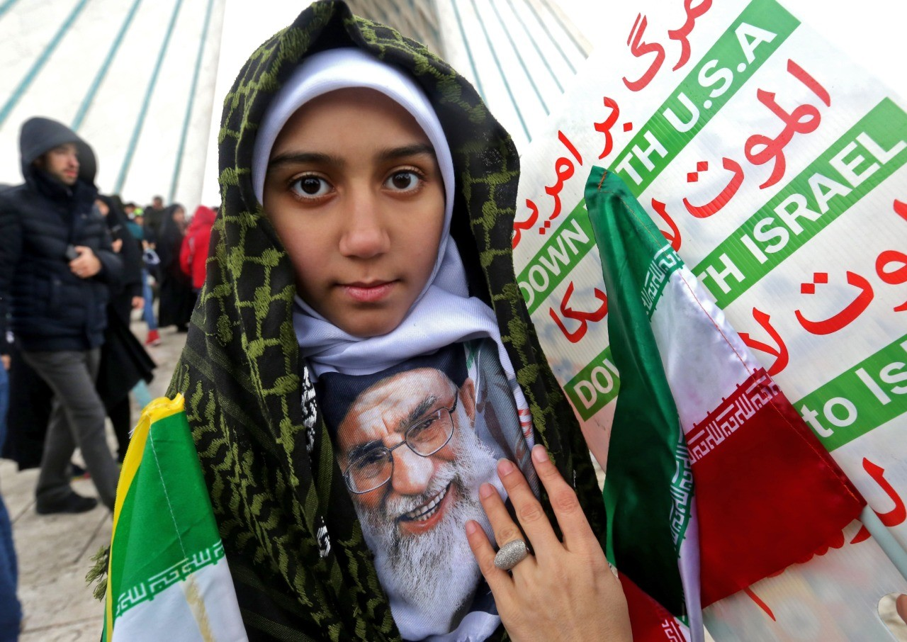 "An Iranian girl poses with a potrait of the country's Supreme Leader Ali Khamenei with signs reading ""Down with USA"" and ""Down with Israel"" during a ceremony celebrating the 40th anniversary of Islamic Revolution by the capital Tehran's Azadi (Freedom) tower in the square of the same name on February 11, 2019. (Photo by ATTA KENARE / AFP) (Photo credit should read ATTA KENARE/AFP/Getty Images)"