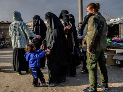 Veiled women, reportedly wives and members of the Islamic State, walk under the supervision of a female fighter from the Syrian Democratic Forces (SDF) at al-Hol camp in al-Hasakeh governorate in northeastern Syria on February 17, 2019. (Photo by BULENT KILIC / AFP) (Photo credit should read BULENT KILIC/AFP/Getty Images)
