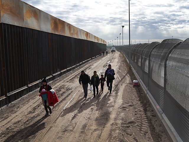 "EL PASO, TEXAS - FEBRUARY 01: Central American immigrants walk between a Bollard-style border fence, left, and the older ""legacy"" fence after crossing the Rio Grande from Mexico on February 01, 2019 in El Paso, Texas. The migrants later turned themselves in to U.S. Border Patrol agents, seeking political asylum …"