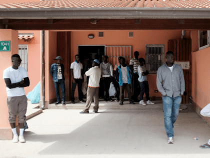 Migrants stand at the Cara Mineo, a hosting centre for asylum seekers, where about 3,200 migrants from North Africa, Ivory Coast, Pakistan, Syria, Afghanistan and other countries are staying in Mineo in the the province of Catania in Sicily on April 21, 2015, three days after a migrant boat capsized …