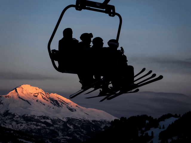 TOPSHOT - Skiers are seen in silhouette on a ski lift as the sun rises next the resort of Lenzerheide, eastern Switzerland, on January 28, 2018. (Photo by Fabrice COFFRINI / AFP) (Photo credit should read FABRICE COFFRINI/AFP/Getty Images)